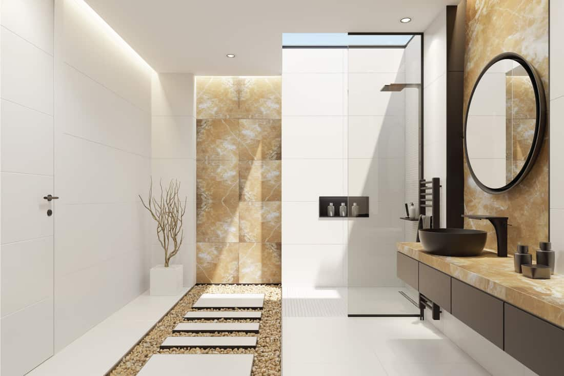 bathroom with a skylight and natural, polished, gold onyx wall tiles, large and narrow white matte ceramic tiles and black details