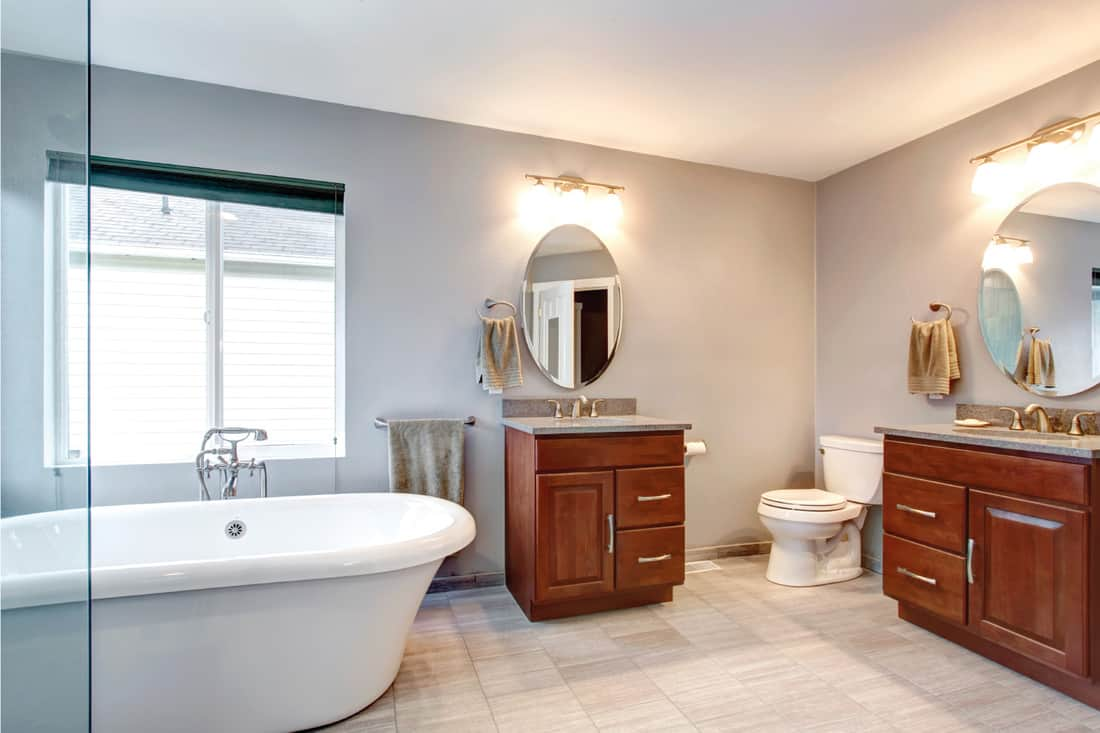 beautiful new luxury bathroom with two sinks with lighting above the vanity mirror
