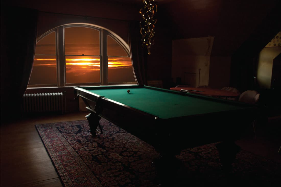 billiard table in a recreation room with rug underneath