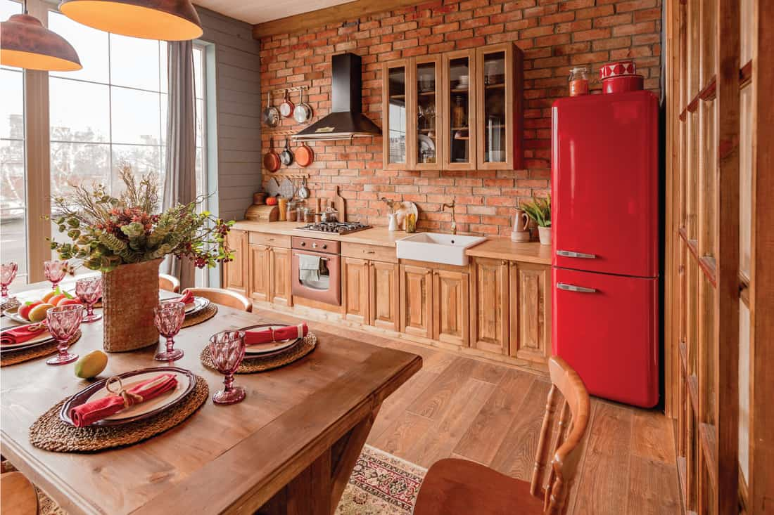 country house in a wooden design, spacious living room with kitchen area and large windows, bedroom on the second floor. Brick red country kitchen