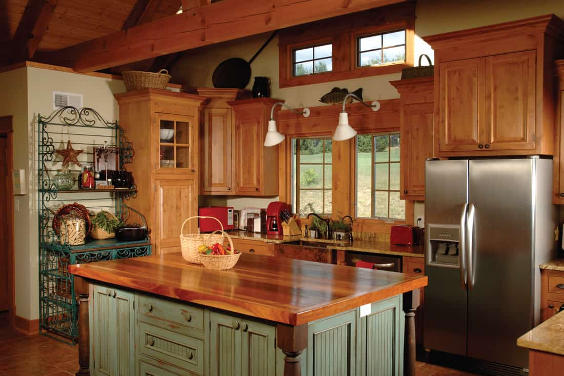 country kitchen with a beautiful wooden butcher table. Warm natural wood country kitchen