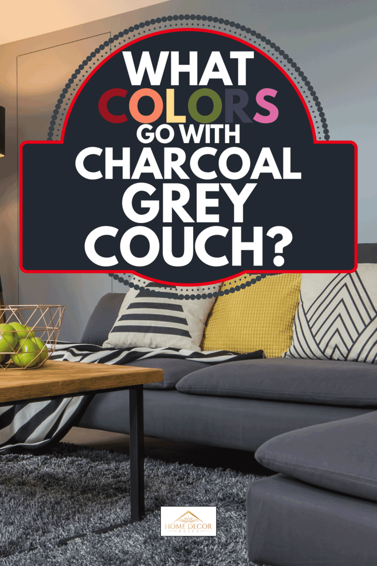 cozy living room with charcoal gray couch, yellow throw pillows, wood coffee table, floor lamp, gray wall. What Colors Go With Charcoal Grey Couch