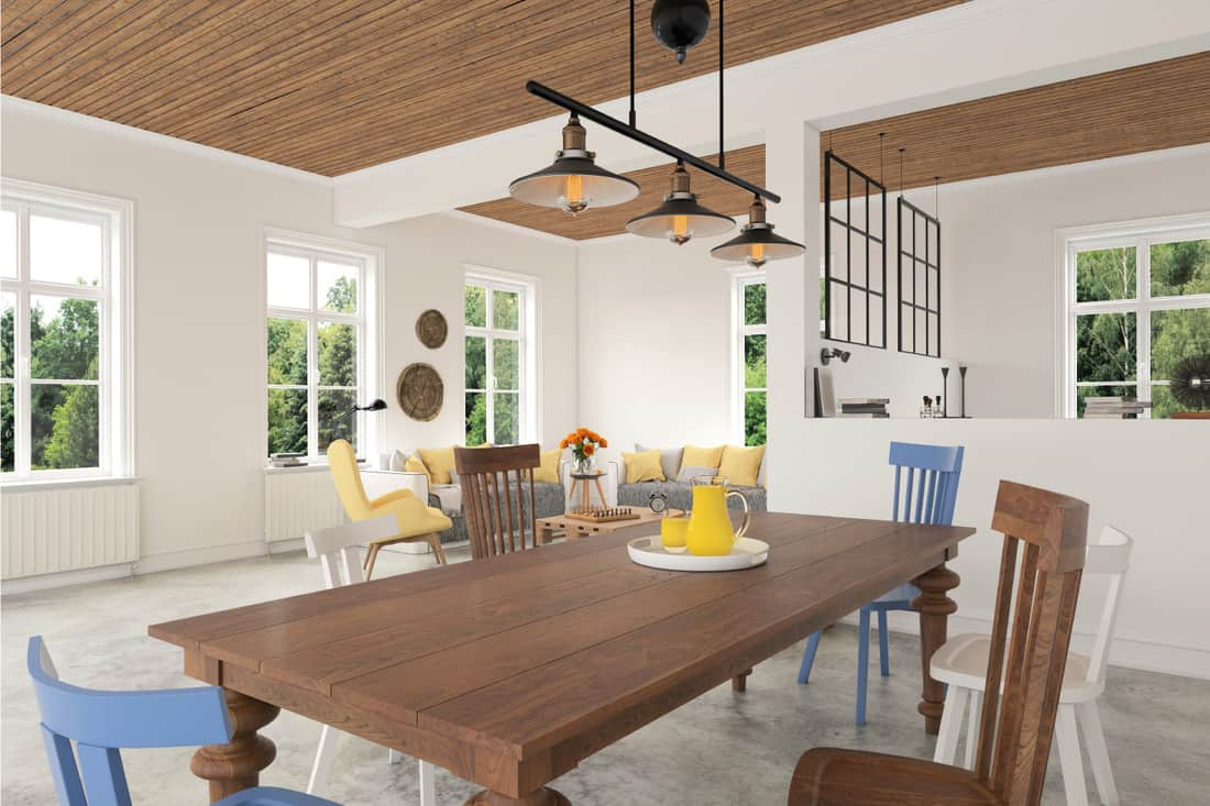 Dining room with oak table, brown white and blue chairs. pendant lights