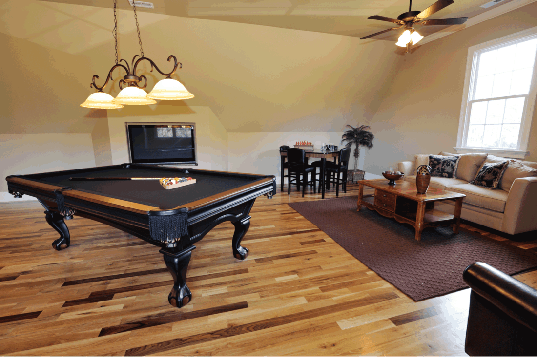 Game room with pool table, wooden floor, pendant lights, couch and coffee table on brown area rug next to small glass round table with chairs