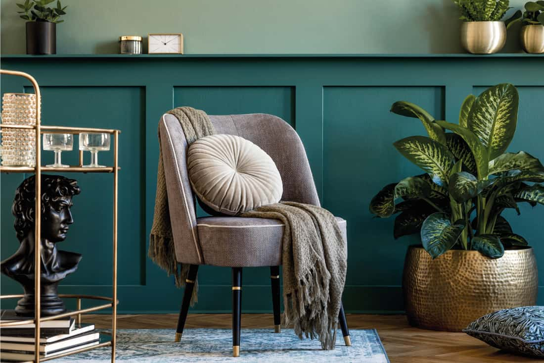 Gray armchair, gold liquor cabinet, plants and elegant accessories, green wall paneling with shelf