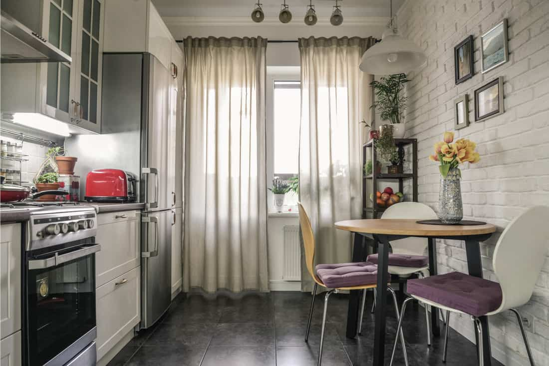 kitchen in Scandinavian style with white furniture and a dining table. high and wide curtains on low windows