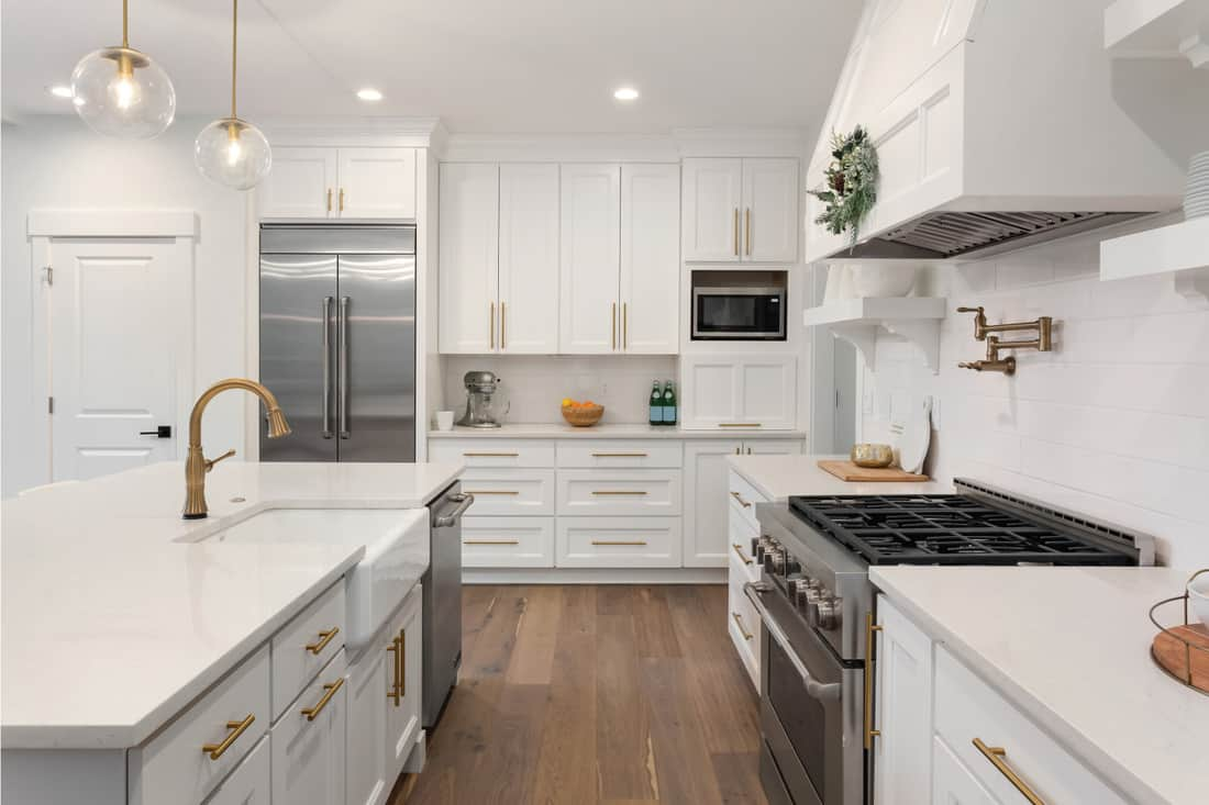 kitchen in newly constructed luxury home with white cabinets and dark wood floors