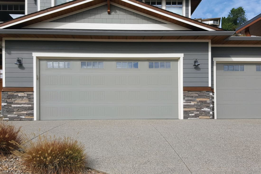 Large home garage with gray doors, paved driveway