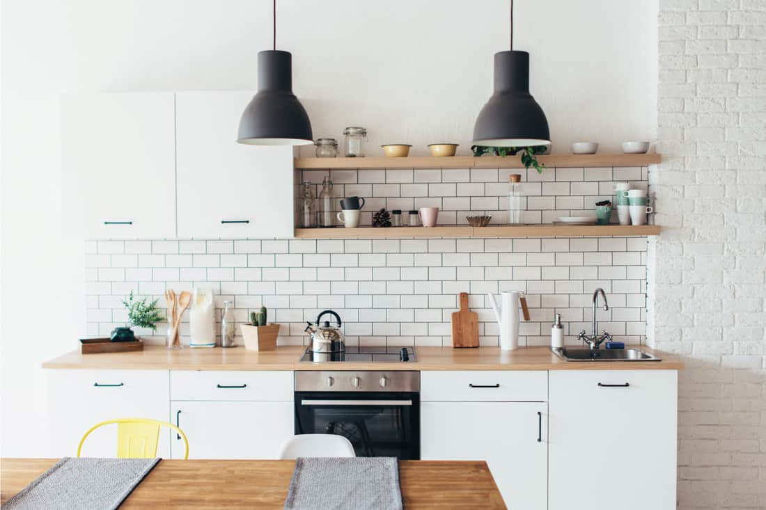 light interior of kitchen with white furniture and dining table. kitchen sink at the end of the countertop