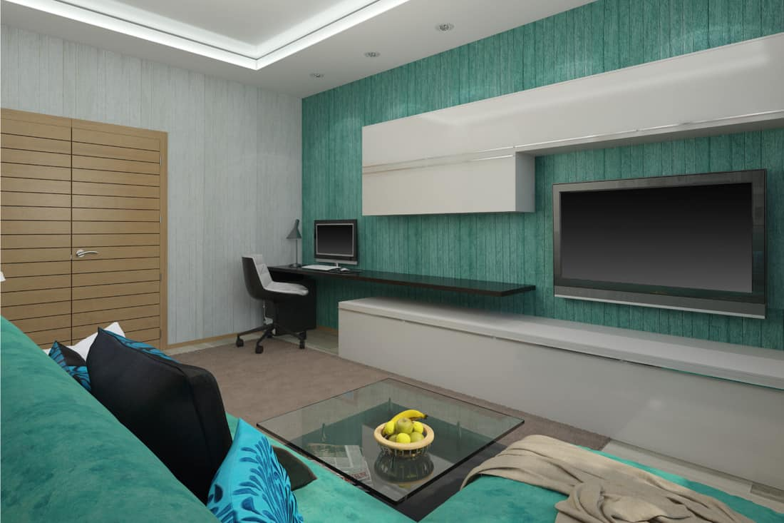 Living room in a turquoise color with sea foam green wallpaper and matching couch