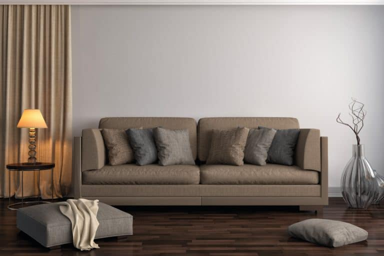 living room with dark brown wood floor, brown sofa, ottoman, throw pillows. 11 Color Schemes For Living Room With Brown Sofa