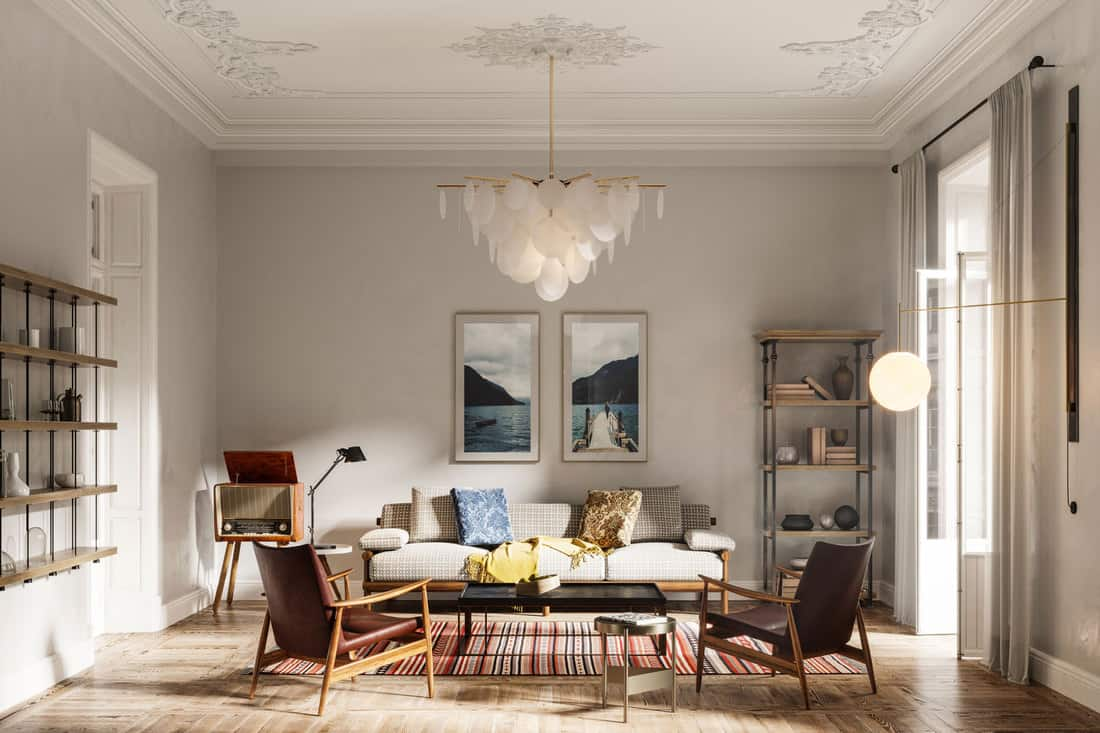 living room with sofa set, arms chairs, wall paintings and beautiful chandelier, Should Furniture Touch The Wall?
