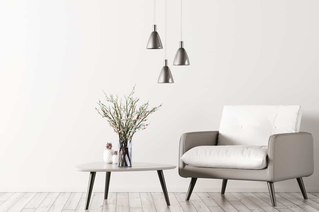Living room with triangular coffee table, pendant lamps and white grey armchair, roomy high armchair
