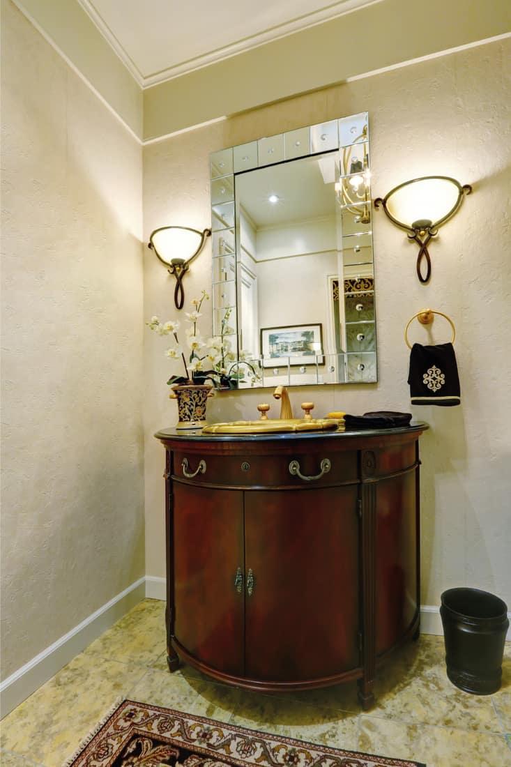 luxury bathroom with vanity mirror, golden sink, wood elements, light sconces beside vanity mirror