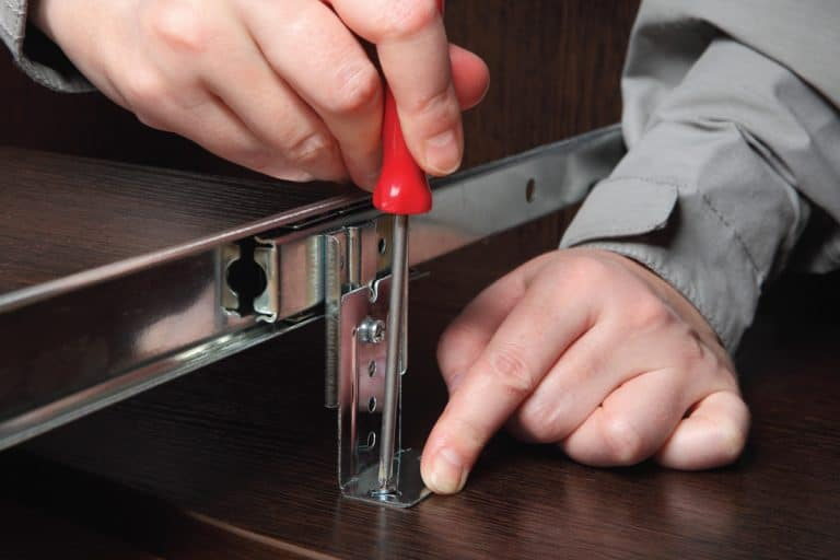 man using philips screw driver to remove parts of a drawer. How To Remove Drawer From Ikea Malm Dressing Table
