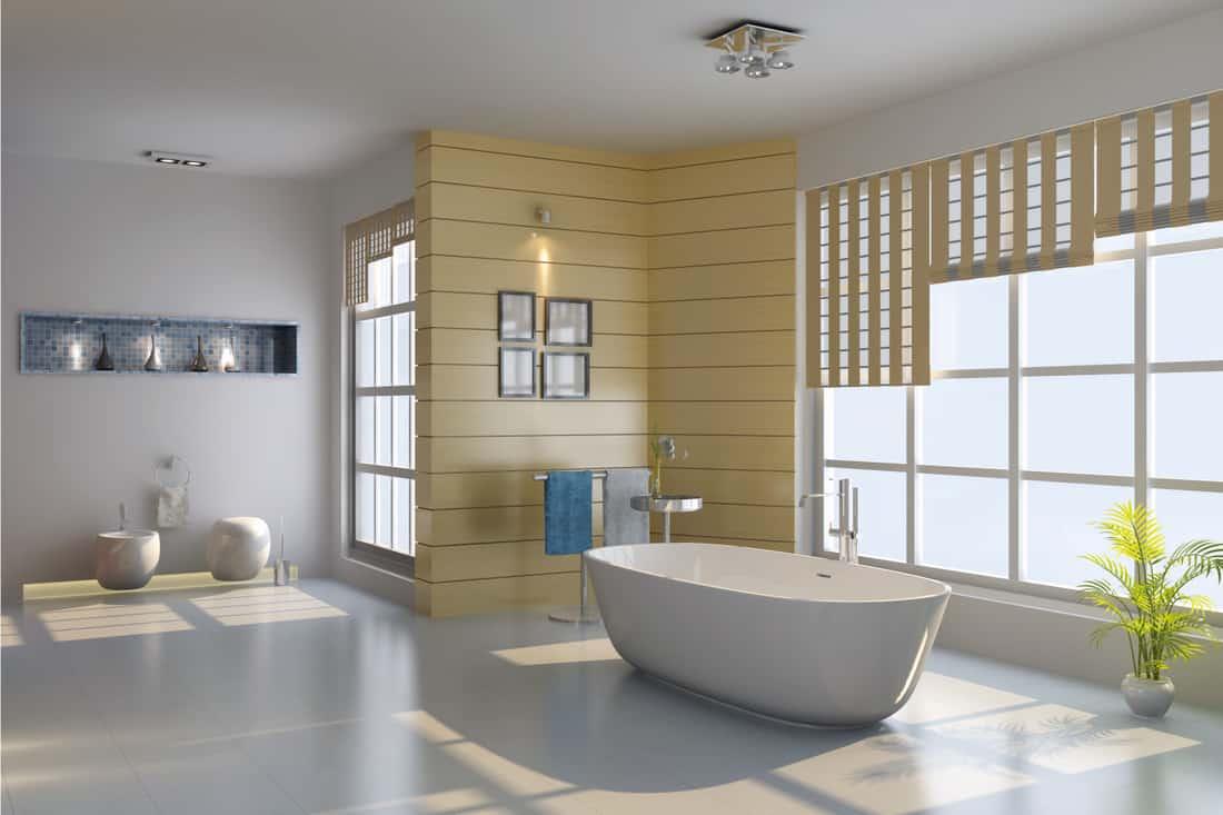 modern bathroom with bathtub, large windows, decorative lighting on framed artwork