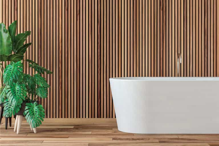 modern bathroom with hardwood parquet floor and wooden paneled wall, free standing bathtub, potted plants on the side. 13 Perfectly Zen Bathroom Ideas