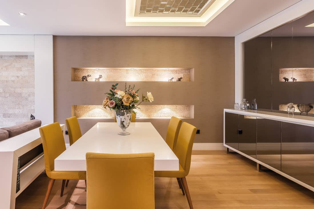 Modern dining room with large glass mirrors, white rectangular table and yellow dining chairs
