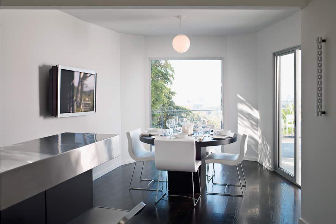 Modern dining room with large glass windows, LCD TV, glass sliding door, bringing the outside in ambiance