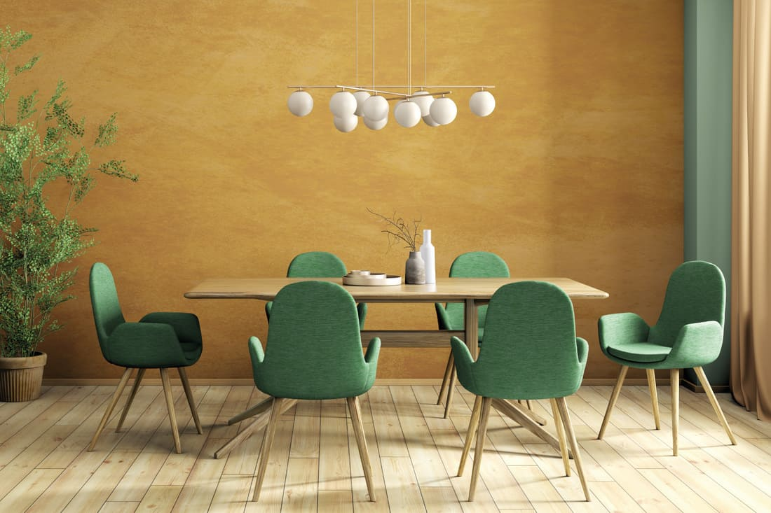 Modern dining room, wooden table and green chairs against orange stucco wall