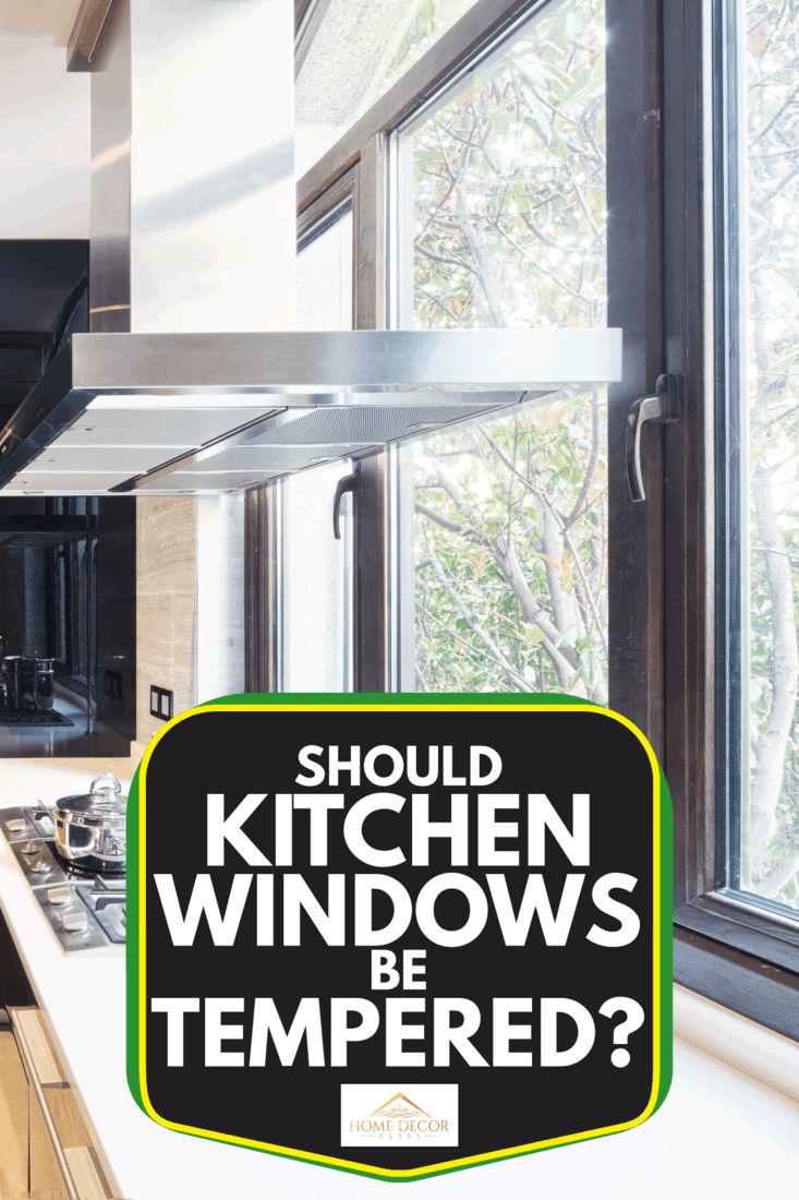 Modern home kitchen with black cabinets, white marble countertop, and large tempered glass windows, Should Kitchen Windows be Tempered?