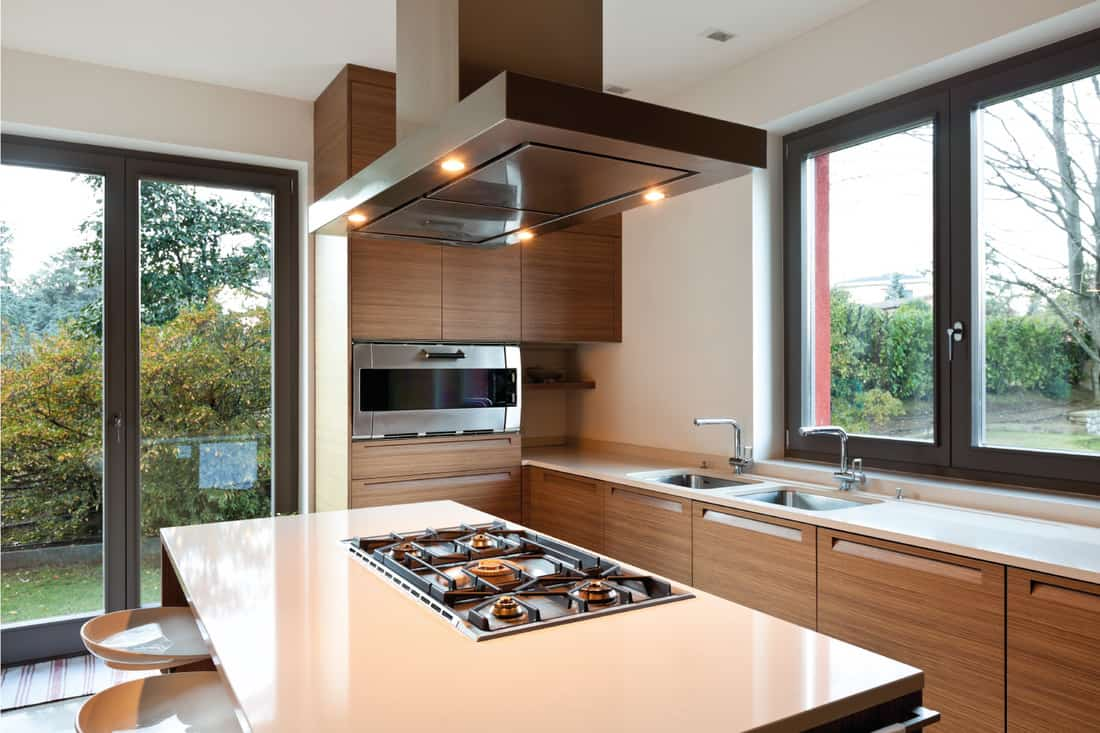 modern kitchen with island, wood accent cabinets, tempered glass windows