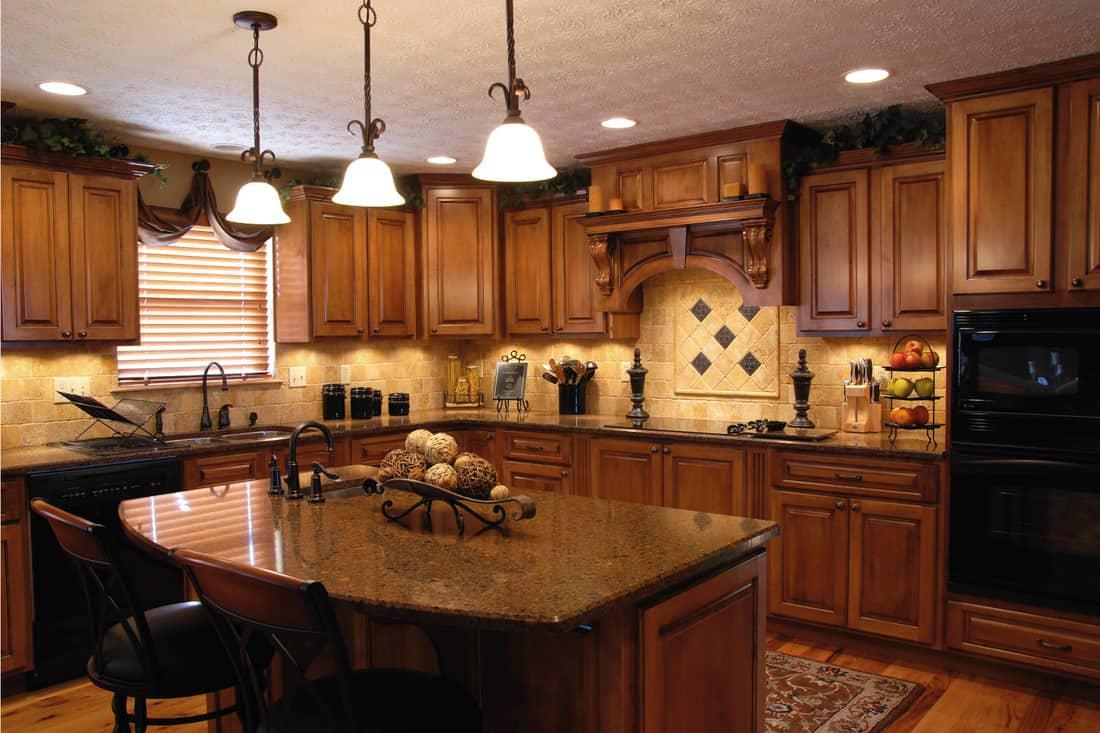 modern kitchen with maple cabinets, island with brown quartz