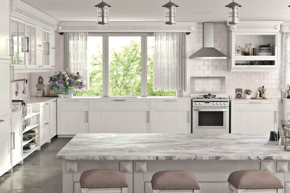 modern kitchen with white cabinets and gray flooring. kitchen island with marble top