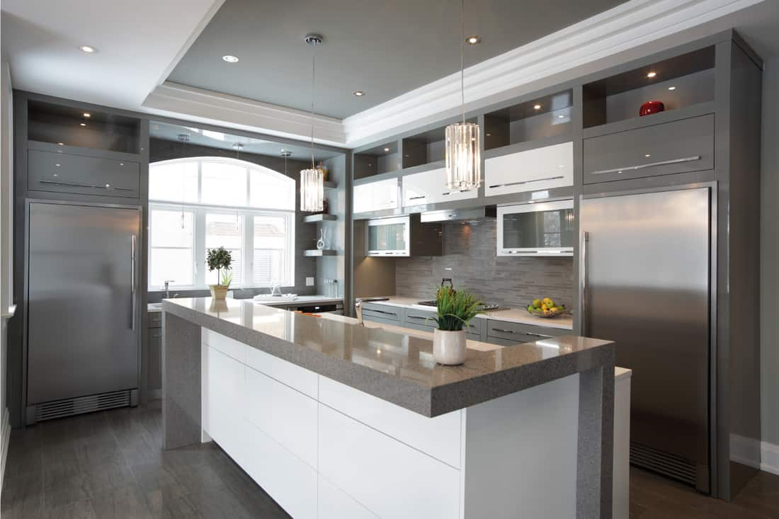 Huge grey kitchen cabinets matching the grey and white countertop and grey floor