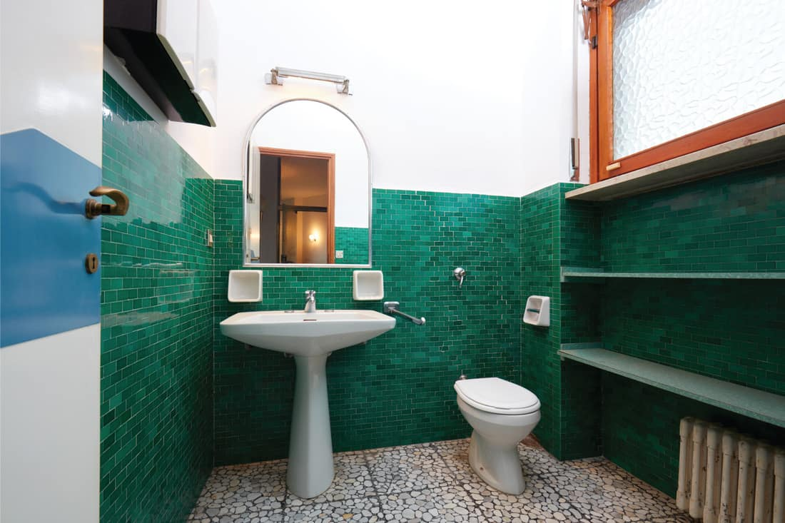 old teal bathroom in an apartment with vanity mirror, sink, toilet, and space heater
