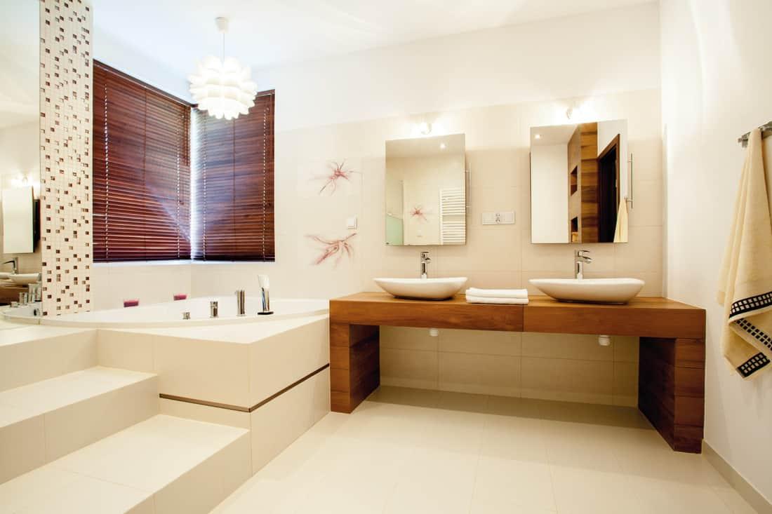 spacious bathroom with decorative lighting above the bathtub