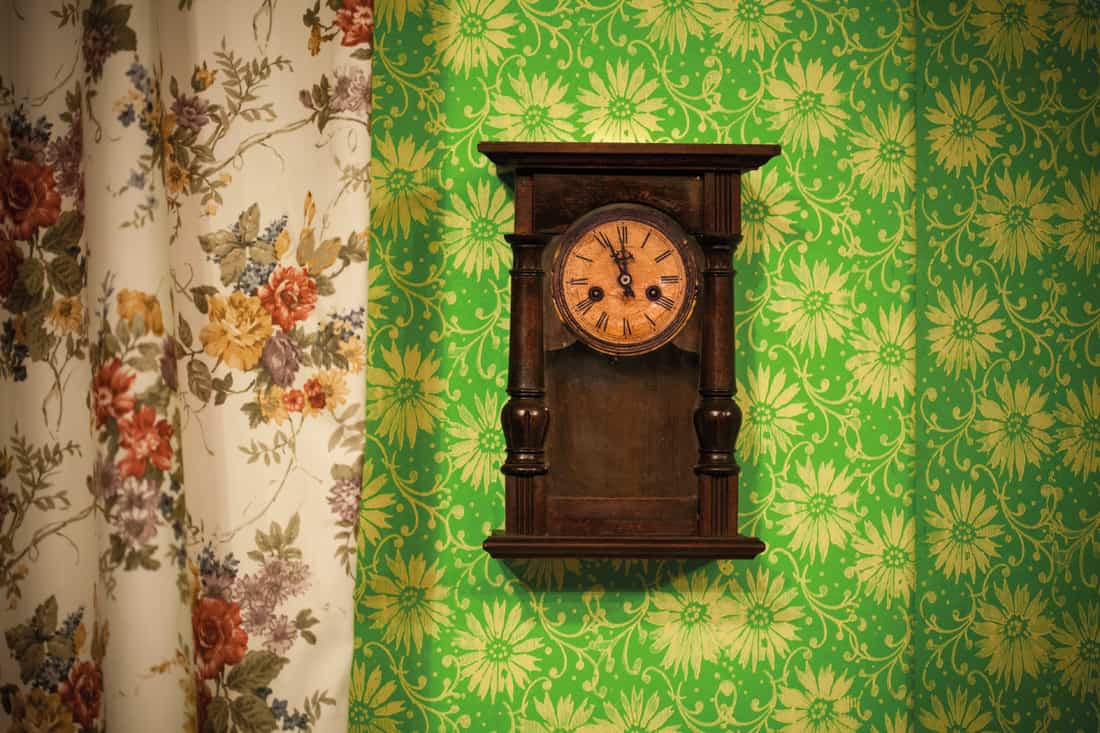 vintage wall clock in a flower pattern wallpaper and curtain