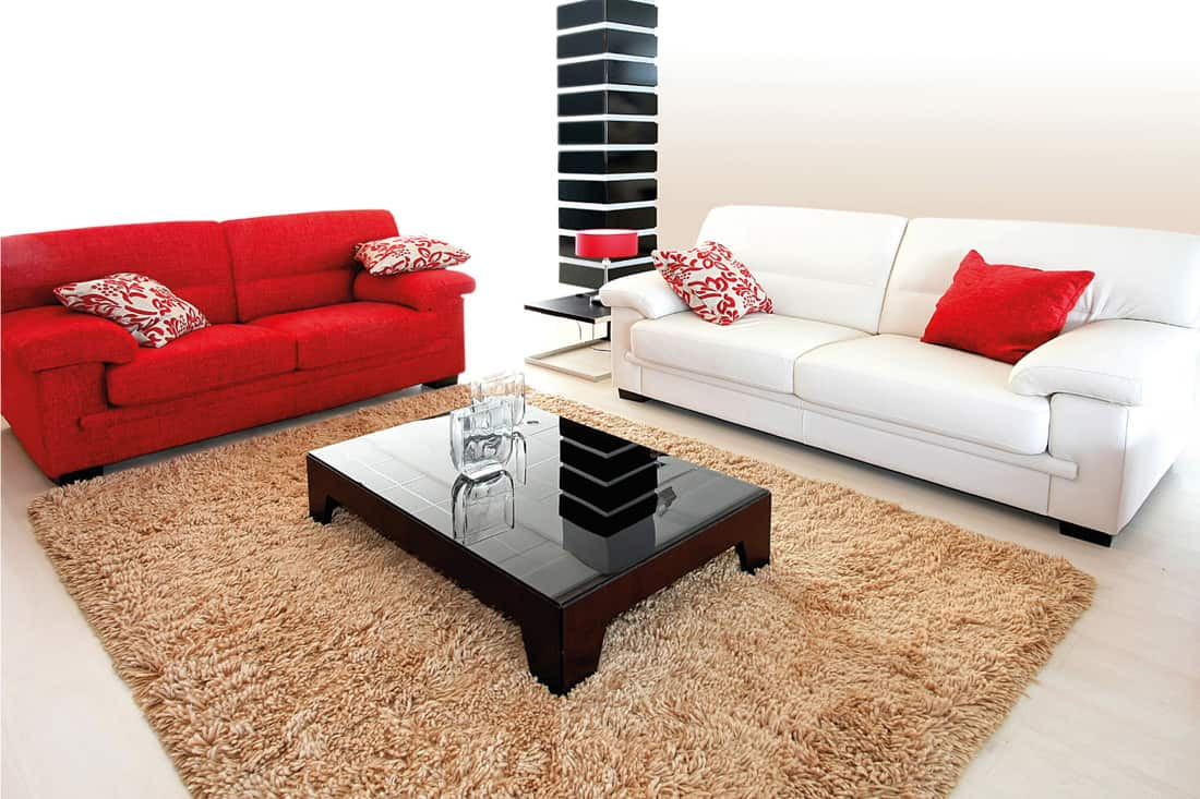 White and red sofa in a living room with brown carpet and dark brown center table