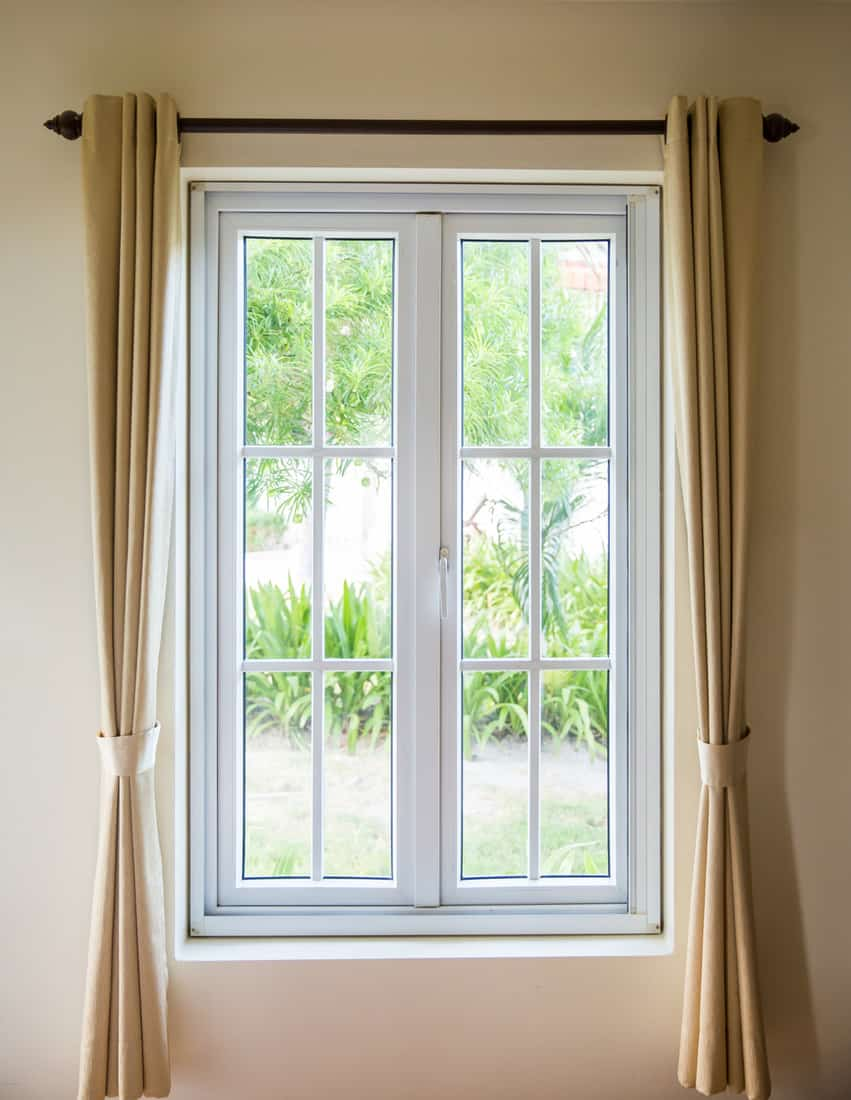 white frame small windows with brown curtain