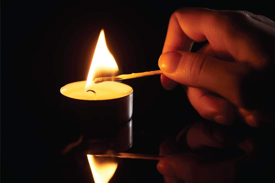 woman lighting up candle with match
