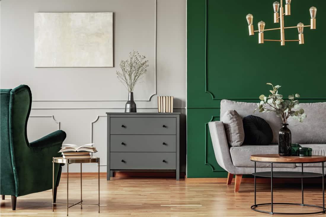 Wooden commode, Scandinavian sofa and emerald green armchair