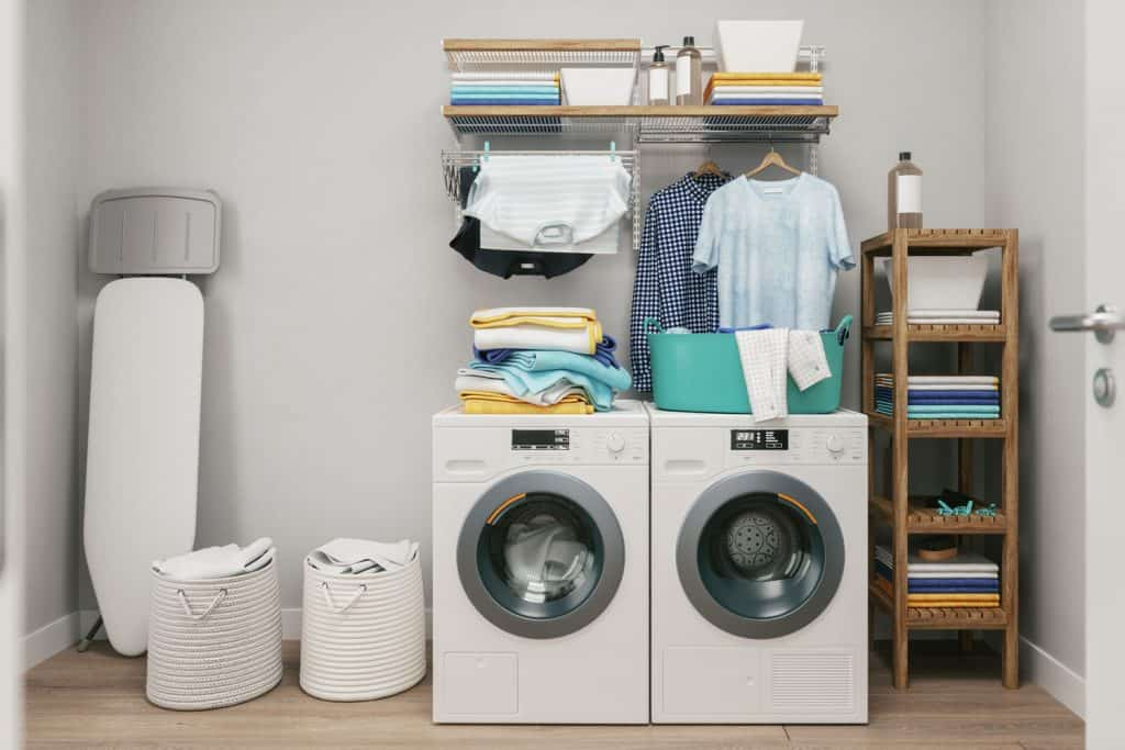 A Scandinavian themed laundry room with two washing machines, a wooden divider, and folded cloths on top