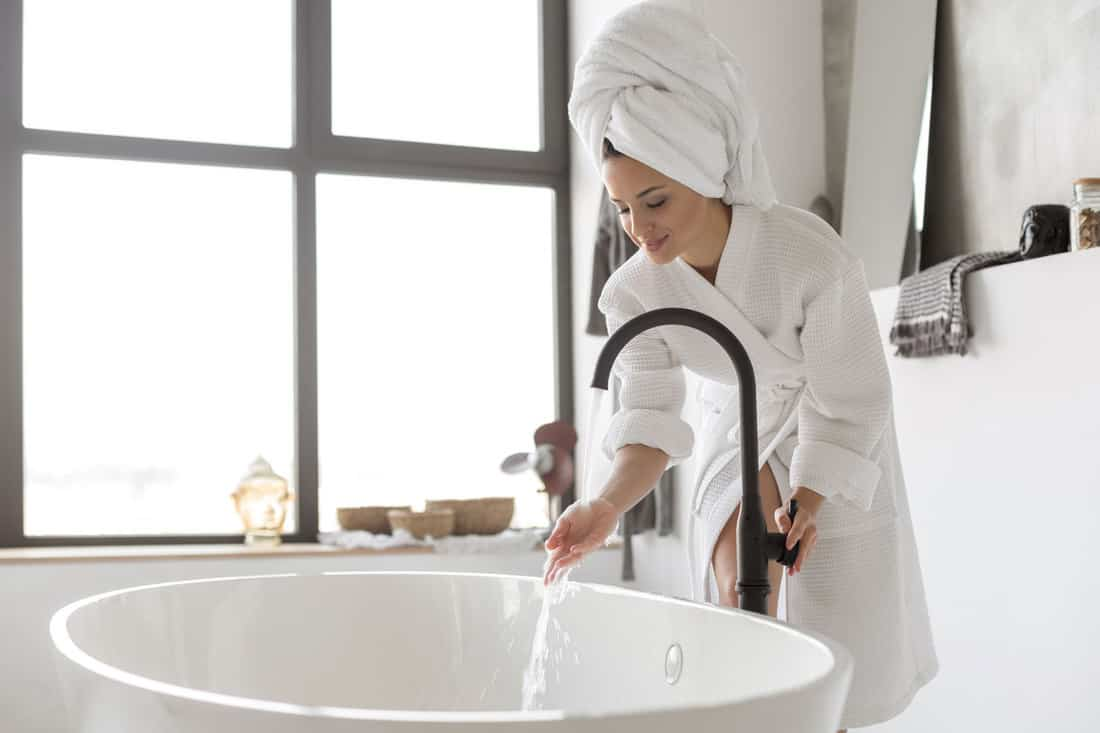 A beautiful lady Turning on the water of bathtub at home, Do Bathtubs Come With Drains?