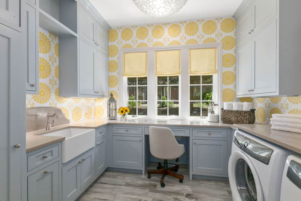 A blue colored laundry room with yellow floral wallpapers and laminated flooring