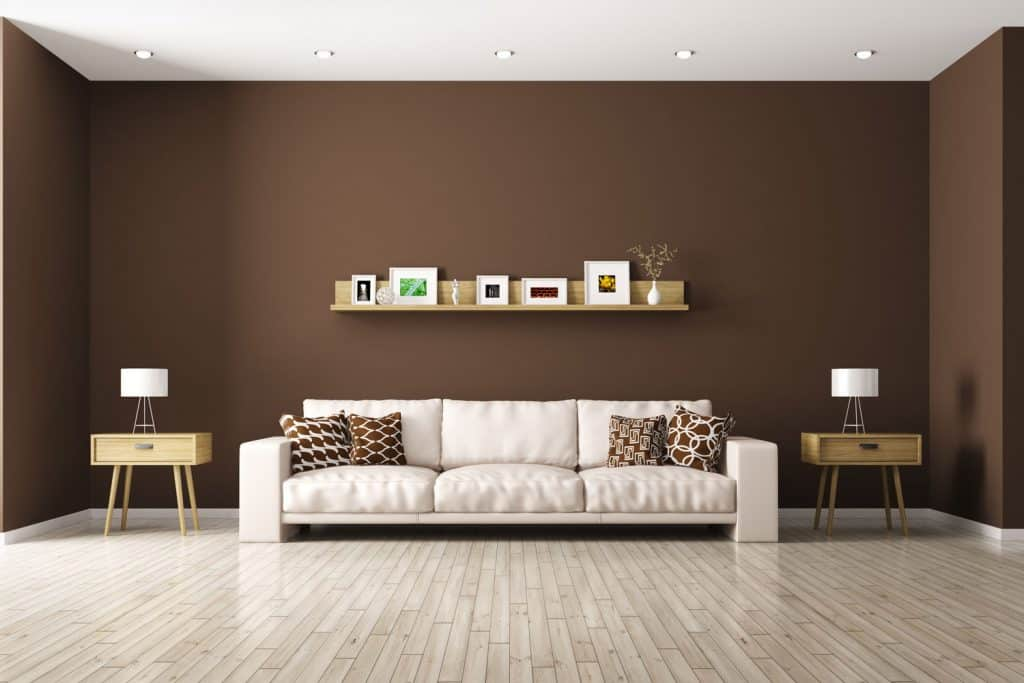 A brown walled living room with a long square armed sectional sofa and end table on the side