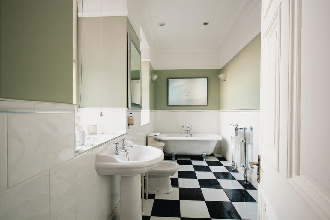 A clean, simple bathroom with a checkered pattern tiled floor in black and white. Sage green painted wall