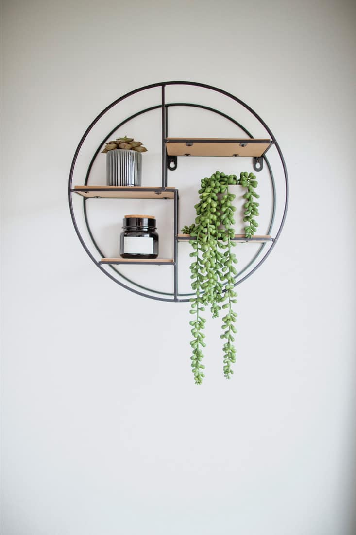 A close-up shot of a circular shelving unit on a white wall in a living room interior.