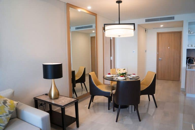 A contemporary themed living room apartment with luxurious dining set, square armed sofa, and a huge ceiling lamp at the dining area, How High Should You Hang A Full-Length Mirror?