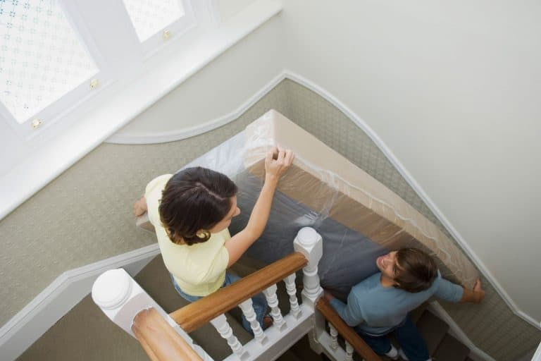 A couple moving a mattress up a narrow stairway, Can You Bend A Mattress To Get It Upstairs?
