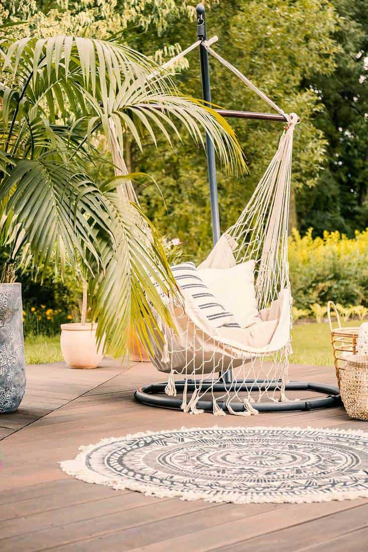 A cozy hammock with pillows on a deck in a green garden during summer vacation in a luxurious hotel