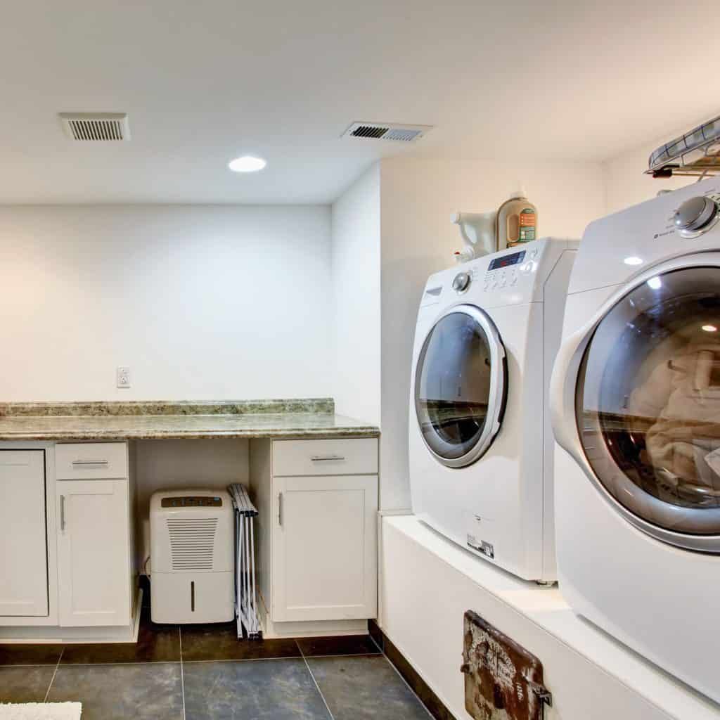 A spin dryer and washing area inside a gorgeous white painted washing room