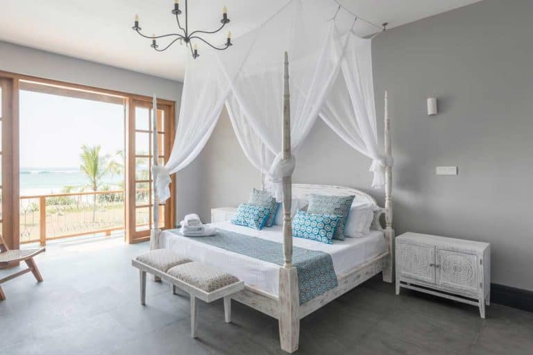 A four poster bed with mosquito net in bright hotel room with beach view on balcony, How Do You Hang Curtains Behind A Bed?