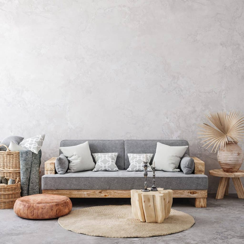 A gorgeous boho inspired living room with a gray faux wall and boho themed furnitures