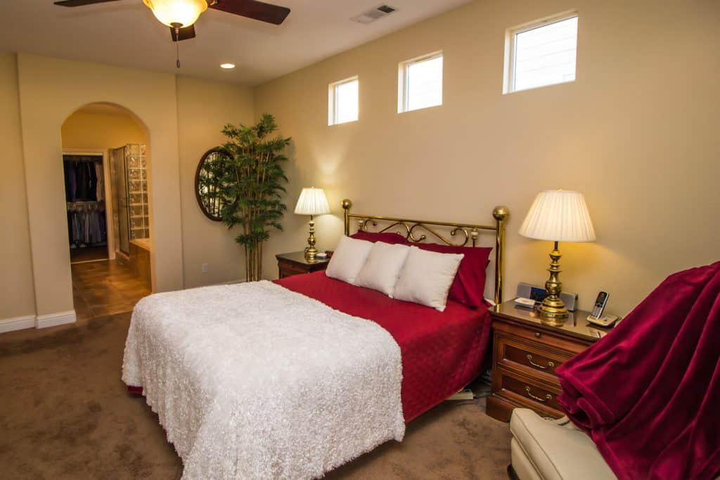 A gorgeous cream colored bedroom with a dark brown carpeted flooring, a king sized gold plated metal bed with white and red beddings