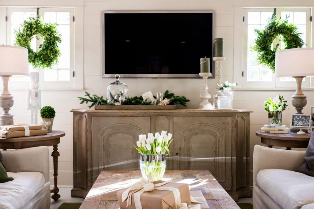 A gorgeous wooden sideboard with indoor plants on the sides, olive wreaths on the window, and a wall mounted on the wall